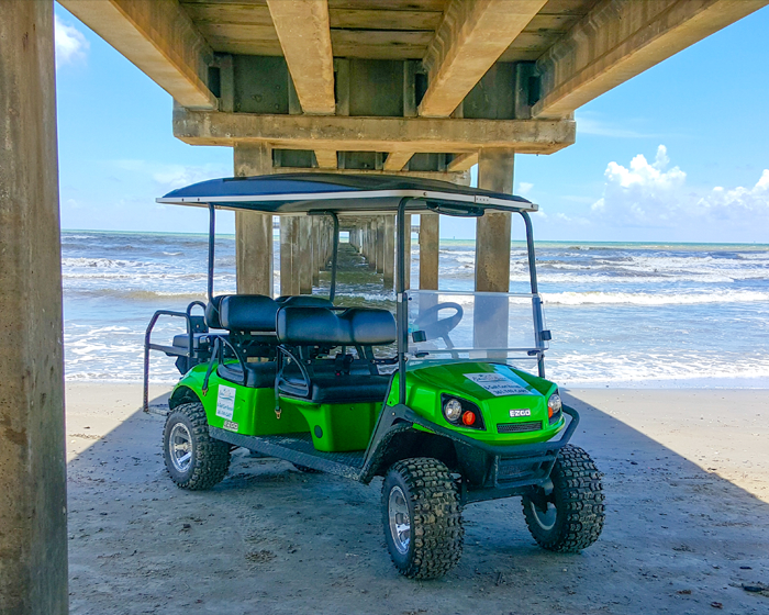 Silver Sands green golf cart under pier in Port Aransas